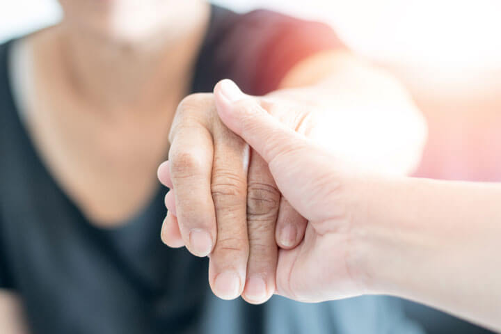 carer hand holding elder hand woman