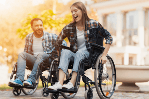 A man and a woman on wheelchairs ride around the park