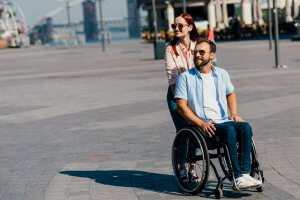 attractive girlfriend in sunglasses pushing disabled handsome boyfriend in wheelchair
